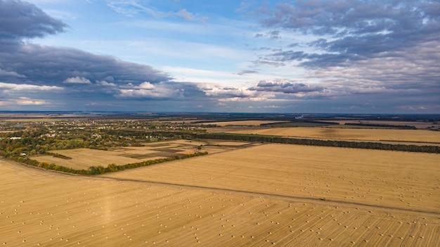 Vista aérea de campos de cereais após a colheita com palheiro e piso de trator