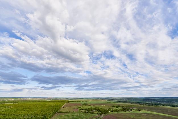 Vista aérea de campos e árvores verdes sob um céu azul com nuvens à luz do sol.