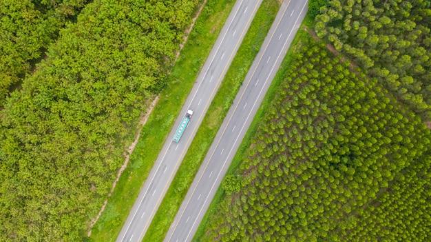 Vista aérea de carros e caminhões na estrada de asfalto passa pela floresta verde