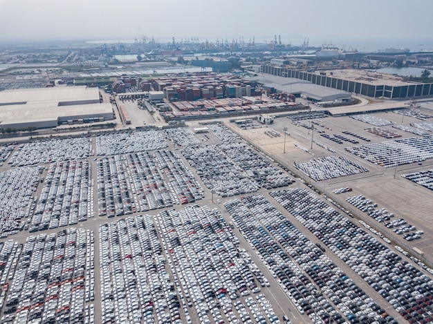 Vista aérea de carros novos estacionados na área de estacionamento da fábrica de automóveis. aguardando exportação e importação no porto internacional.