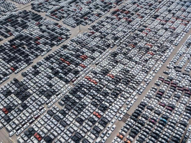 Vista aérea de carros novos estacionados na área de estacionamento da fábrica de automóveis. w