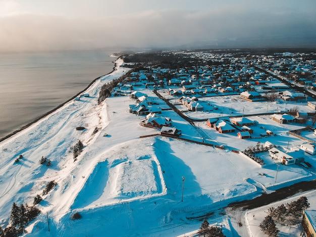 Vista aérea de casas e campo coberto de neve, vendo o corpo de água sob o céu branco