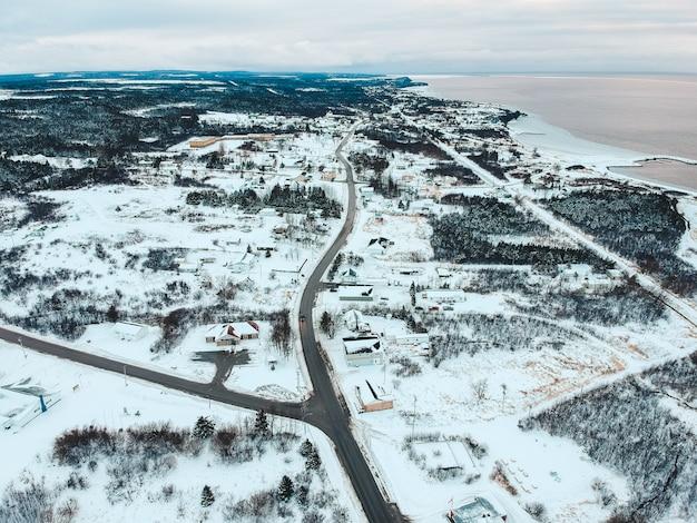 Vista aérea de casas no campo nevado, vendo o corpo de água sob o céu branco e azul