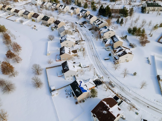 Vista aérea de casas residenciais coberta de neve na temporada de inverno, com neve em estradas e casas cobertas.