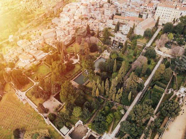 Vista aérea de casas residenciais e árvores durante um dia ensolarado.