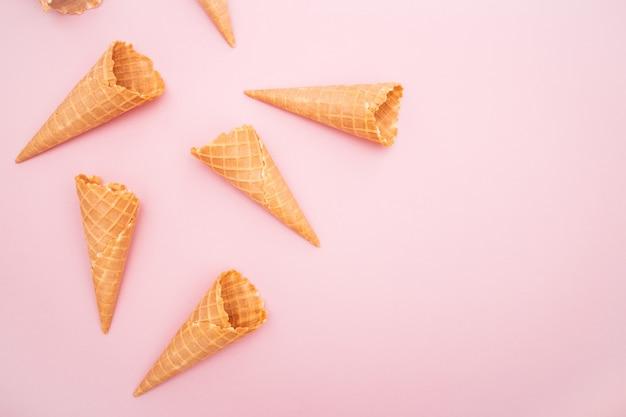 Vista aérea de casquinhas de waffle de sorvete em um fundo rosa