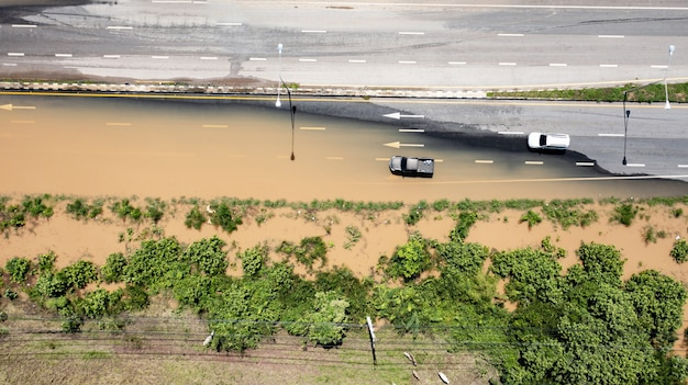 Vista aérea de cima da aldeia inundada e estrada secundária com carro, vista de cima filmada por drone