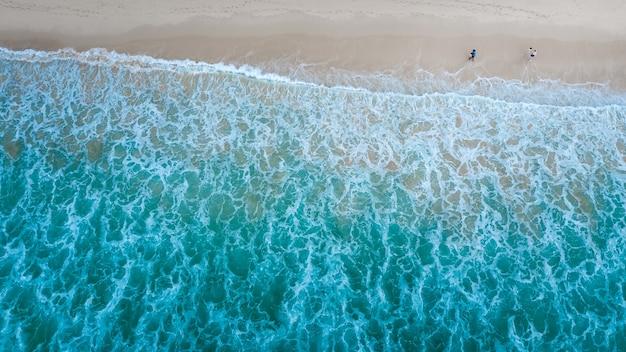 Vista aérea de cima da praia com turistas viajando na bela onda do mar abstrato na praia surin phuket tailândia