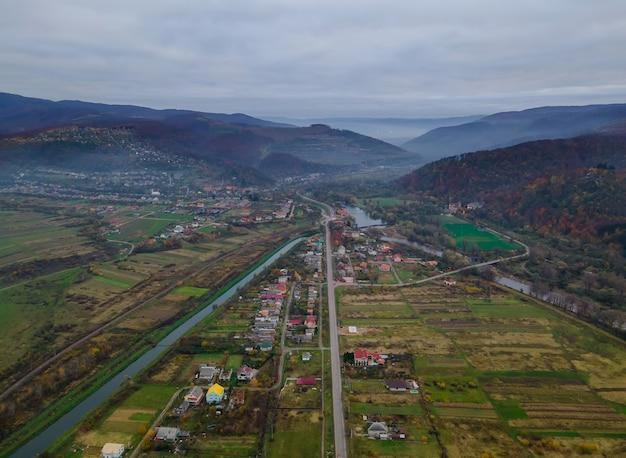 Vista aérea de cima da vila de subúrbio perto da montanha de alta altitude vista aérea de cima para baixo do campo de karpaty