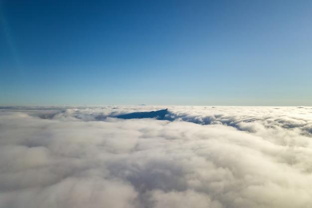 Vista aérea de cima de nuvens brancas fofas e topo de uma montanha distante em um dia ensolarado.