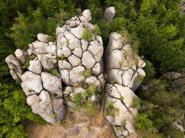 Vista aérea de cima de um drone em uma cidade caverna em uma rocha solitária entre a floresta verde da montanha