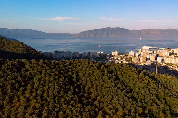 Vista aérea de cima dos campos de oliva na montanha e a costa do mar na cidade da albânia.