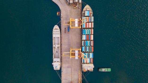 Vista aérea de cima. navio porta-contêineres no cais com ponte de guindaste transporta negócios de importação e exportação em mar aberto.