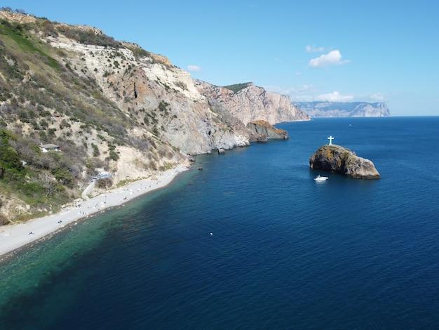 Vista aérea de cima no mar azul e nas costas rochosas pequenas ondas na superfície da água cristalina