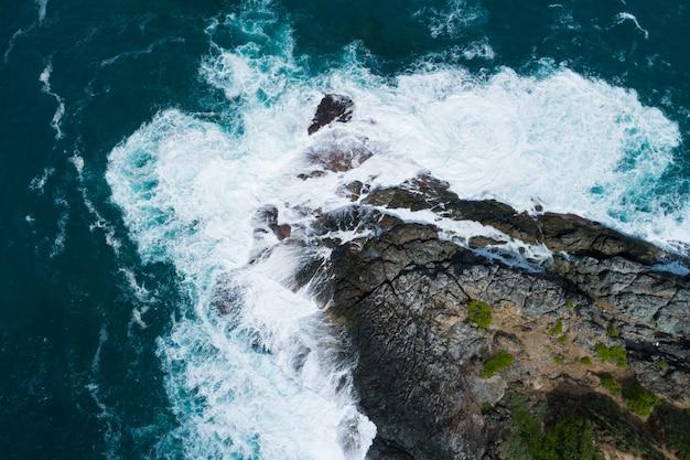 Vista aérea de cima para baixo a onda grande da costa batendo na falésia da rocha superfície do mar escuro e bonita no fundo do verão do dia ensolarado vista superior da vista do mar incrível litoral em phuket, tailândia.