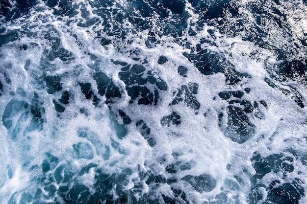 Vista aérea de cima para baixo da superfície da água do mar. a espuma branca acena a textura como um fundo natural.