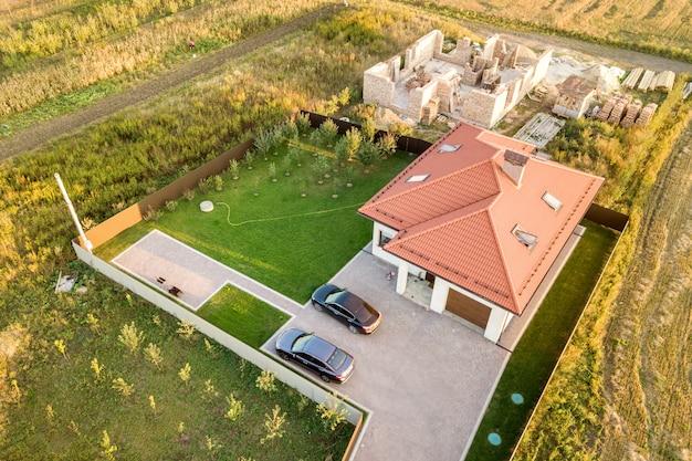 Vista aérea de cima para baixo de duas casas particulares, uma em construção com fundamento de concreto e paredes de tijolo e outra com telhado vermelho.