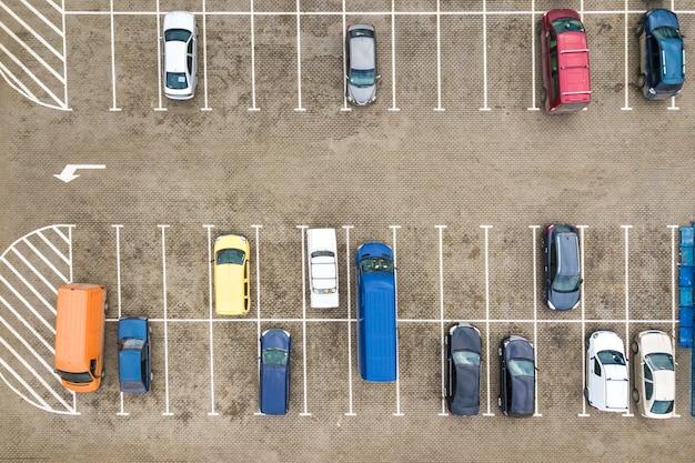 Vista aérea de cima para baixo de muitos carros em um estacionamento de supermercado ou no mercado de revendedor de carros à venda.