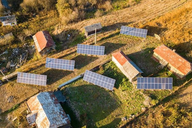 Vista aérea de cima para baixo de painéis solares fotovoltaicos em área rural verde.