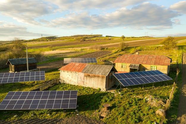 Vista aérea de cima para baixo de painéis solares no quintal de uma vila rural verde