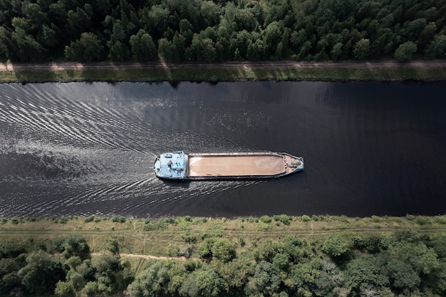 Vista aérea de cima para baixo de uma barcaça automotora sem carga passando por um canal estreito