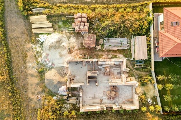 Vista aérea de cima para baixo de uma casa em construção com base de concreto e paredes de tijolos.