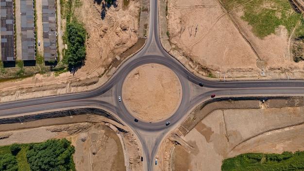 Vista aérea de cima para baixo de uma nova rotatória, tráfego de carros e caminhões na rotatória ...