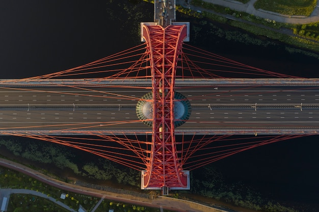 Vista aérea de cima para baixo de uma ponte pênsil em moscou, à luz contrastante do sol nascente, sem carros e pessoas