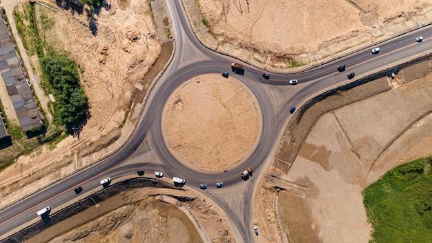 Vista aérea de cima para baixo de uma rotatória de tráfego de carros e caminhões no círculo ...