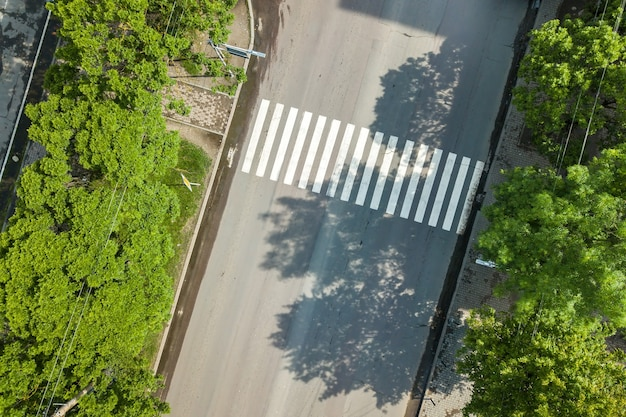 Vista aérea de cima para baixo de uma rua movimentada com o tráfego de carros em movimento e a faixa de pedestres da estrada de zebra.