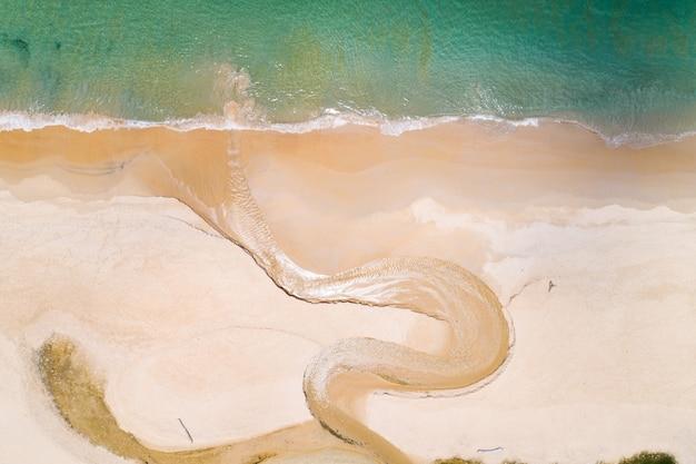 Vista aérea de cima para baixo do rio de curva e da linha de costa em dia de verão.