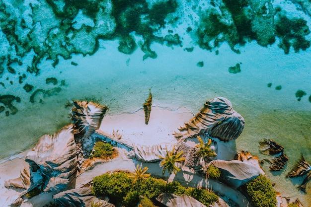 Vista aérea de cima para baixo para ver um paraíso mundialmente famoso, como a praia anse source d argent na ilha la digue, seychelles