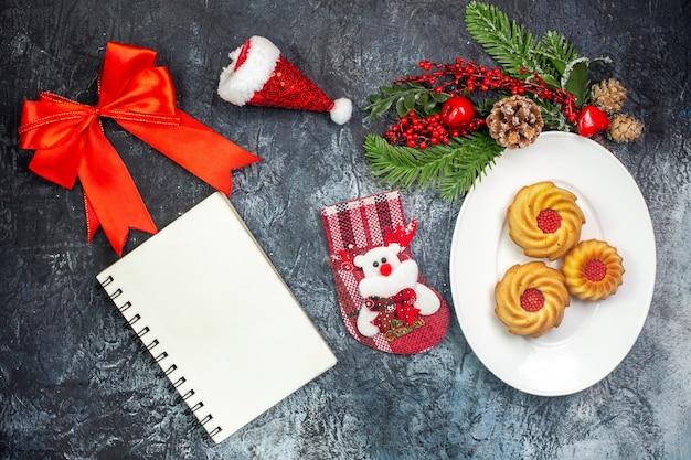 Vista aérea de deliciosos biscoitos em um prato branco e decorações chapéu de papai noel com fita vermelha meia de ano novo ao lado do caderno na superfície escura