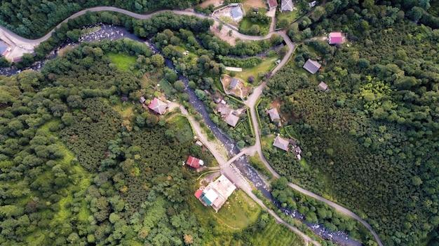 Vista aérea de drone da natureza no vale da geórgia, com rio estreito e encostas de colinas de vilarejo