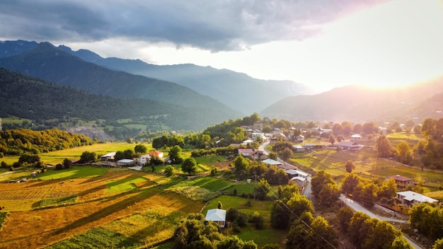 Vista aérea de drone de uma vila na geórgia ao pôr do sol valley fields e edifícios, montanhas e colinas