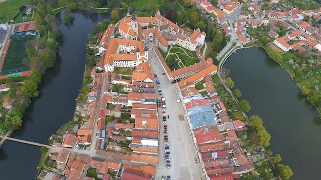 Vista aérea de edifícios coloridos com telhados de telha vermelha na praça medieval e o castelo velho em telc, república tcheca