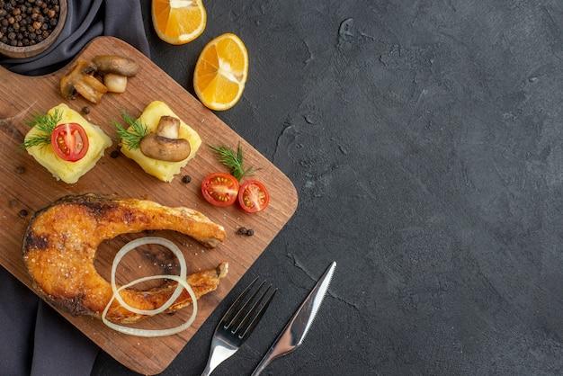 Vista aérea de farinha de peixe frito com cogumelos, vegetais, queijo, tábua de madeira, fatias de limão, pimenta em toalha de cor escura talheres em superfície preta afligida