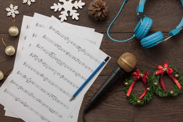 Vista aérea de feliz natal e conceito de fundo de música. decorações emocionais e ornamento com notas brancas de papel.objetos em mesa marrom rústica moderna em estúdio caseiro. artigos essenciais para a temporada.