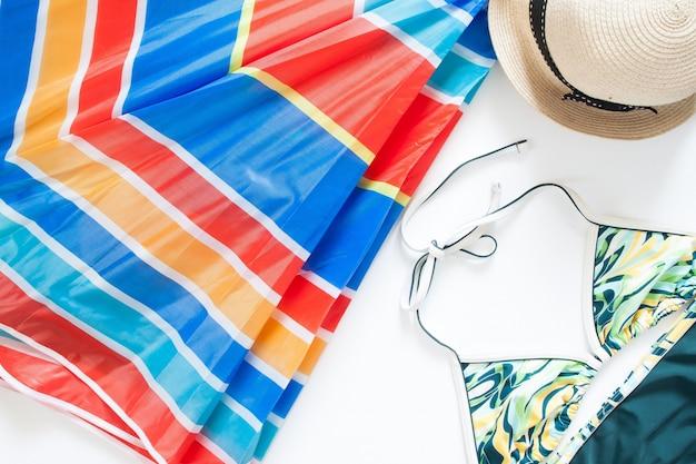 Vista aérea de itens de verão com guarda-chuva colorido, traje de banho e chapéu no fundo branco