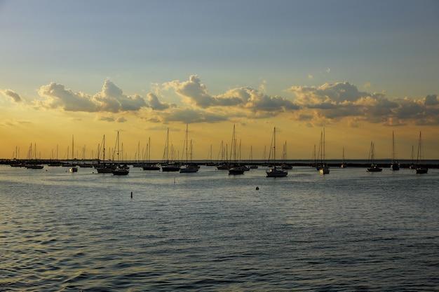 Vista aérea de lindos barcos de barcos coloridos para a baía do oceano com contra o pôr do sol.