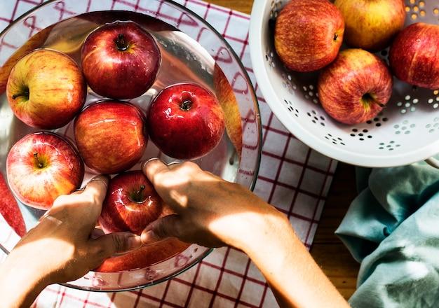 Vista aérea de mãos lavando maçãs na tigela