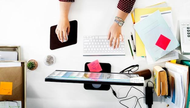 Vista aérea de mãos trabalhando em um computador em uma mesa branca no escritório