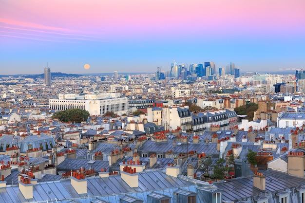 Vista aérea de montmartre sobre os telhados de paris e o distrito comercial de la defense com lua cheia ao nascer do sol, paris, frança