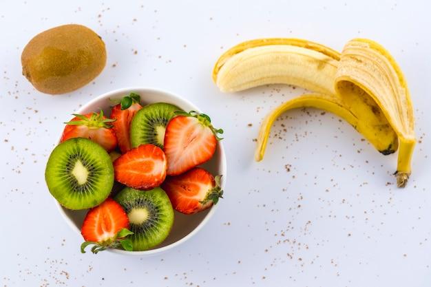 Vista aérea de morangos cortados e kiwis em um prato branco no branco ao lado de um kiwi e uma banana