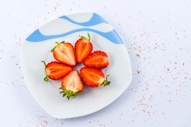 Vista aérea de morangos cortados num prato branco sobre branco com açúcar mascavo
