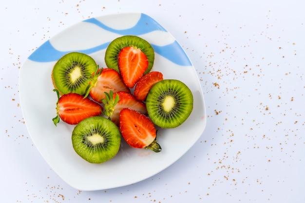 Vista aérea de morangos fatiados e kiwis em um prato branco sobre branco