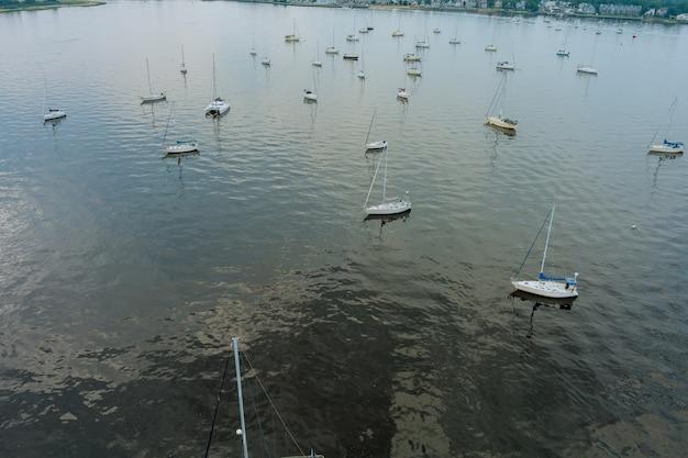 Vista aérea de muitos iates oceânicos com mastros estacionando e flutuando