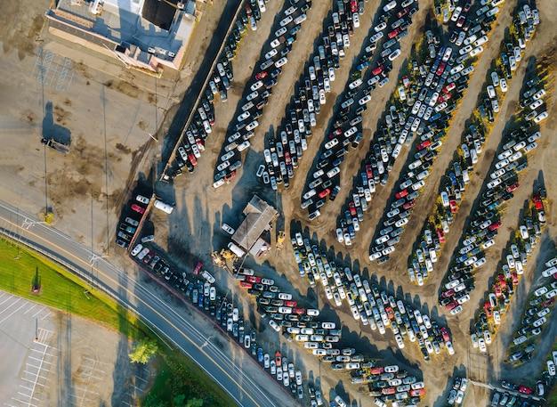 Vista aérea de muitos lotes de leilão de carros usados estacionados distribuídos em um estacionamento.
