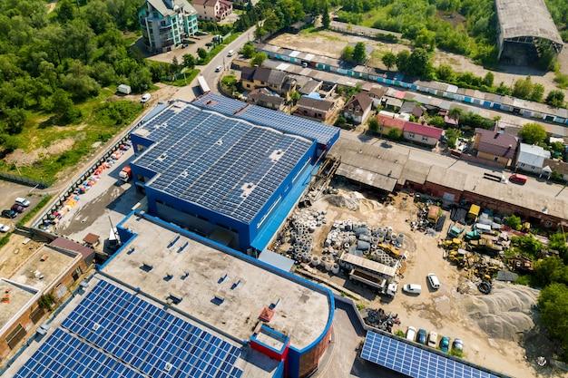 Vista aérea de muitos painéis solares foto voltaicos montados no telhado do edifício industrial.