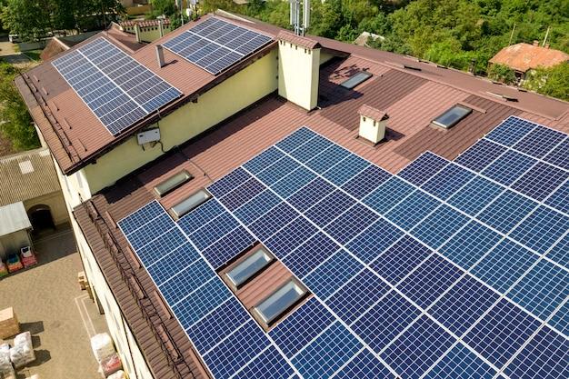 Vista aérea de muitos painéis solares montados no telhado do edifício industrial.